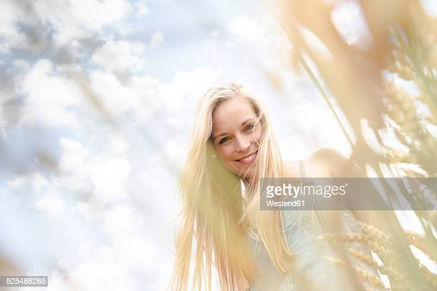 Portrait of smiling young woman standing in a rye field
