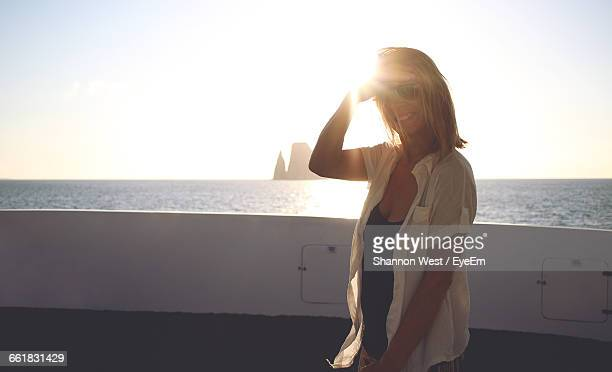 Portrait Of Smiling Young Woman Standing In Cruise Ship Against Clear Sky During Sunset