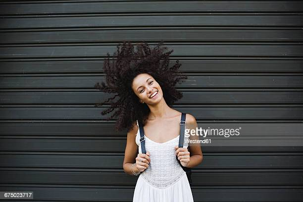 Portrait of smiling young woman standing in front of roller shutter shaking her head