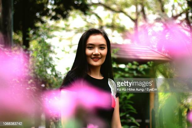 portrait of smiling young woman standing in park - ko ko htike aung stock pictures, royalty-free photos & images