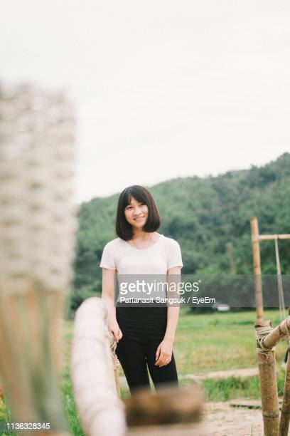 portrait of smiling young woman standing on field - pattanasit stock pictures, royalty-free photos & images