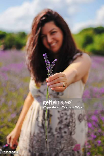 portrait of smiling young woman standing on field,surrey,united kingdom,uk - wayne gerard trotman stock pictures, royalty-free photos & images