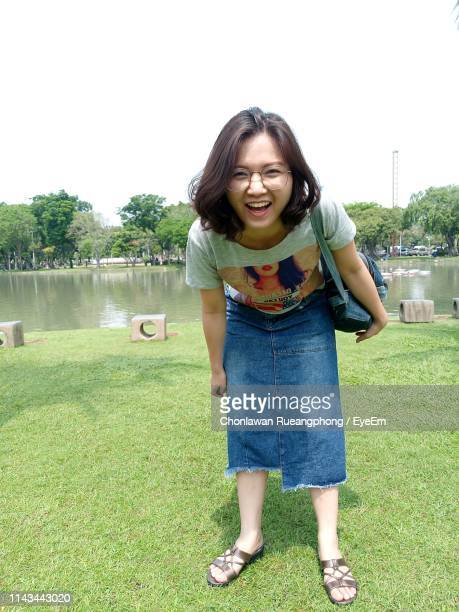 Portrait Of Smiling Young Woman Standing On Grass