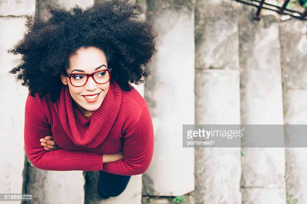 portrait of smiling young woman standing on stairs - red stock pictures, royalty-free photos & images
