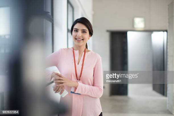 portrait of smiling young woman standing on the corridor in office - nameplate stock pictures, royalty-free photos & images