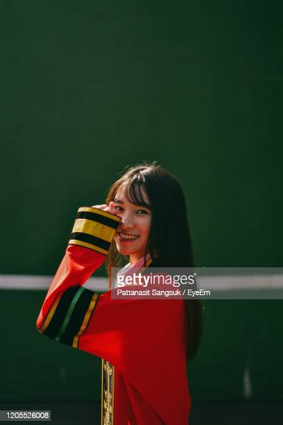 portrait of smiling young woman standing outdoors - pattanasit stock pictures, royalty-free photos & images