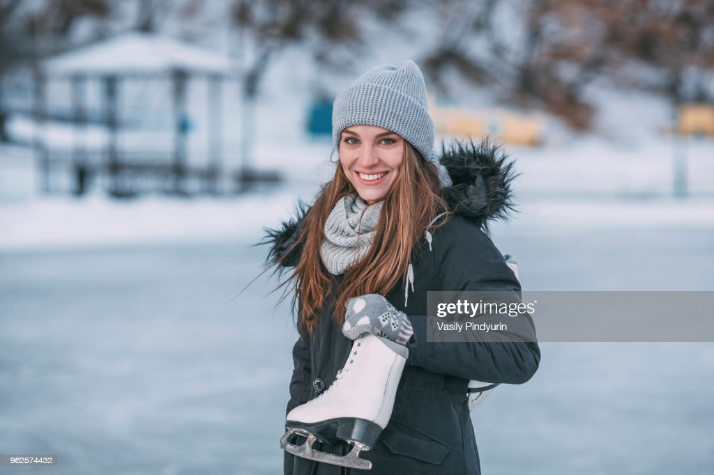 Portrait of smiling young woman standing with ice skate : Stock Photo
