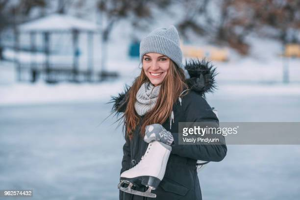 Portrait of smiling young woman standing with ice skate