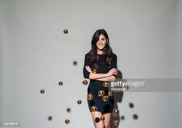 portrait of smiling young woman surrounded by christmas baubles floating mid-air - vestido preto - fotografias e filmes do acervo