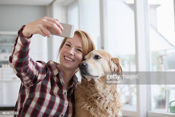 Portrait of smiling young woman taking a selfie with her dog