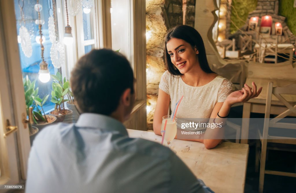 Portrait of smiling young woman talking to her boyfriend in a restaurant : Stock Photo