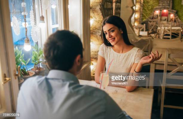 portrait of smiling young woman talking to her boyfriend in a restaurant - daten stockfoto's en -beelden