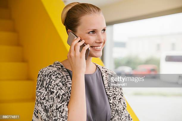 Portrait of smiling young woman telephoning with smartphone in front of yellow stairs