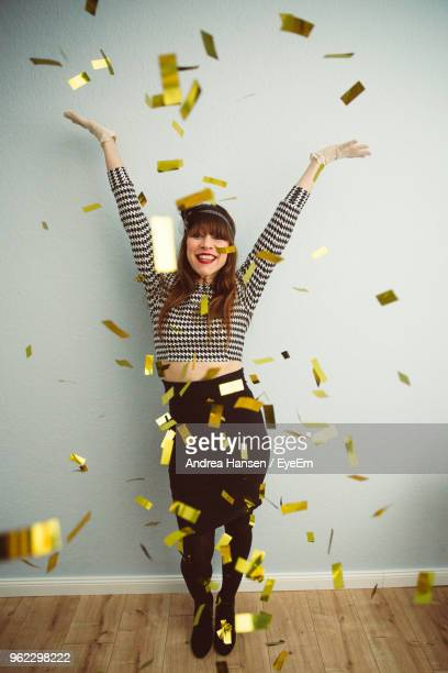 portrait of smiling young woman throwing confetti while standing against wall - gold confetti stock photos and pictures