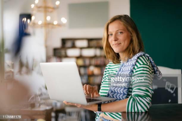 portrait of smiling young woman using laptop in a cafe - independência imagens e fotografias de stock