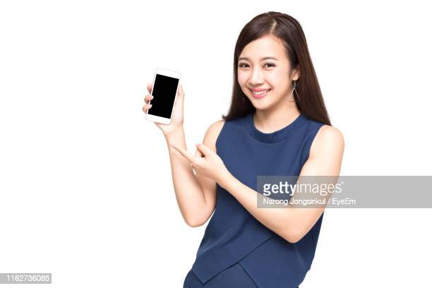 portrait of smiling young woman using mobile phone against white background - 手に持つ ストックフォトと画像