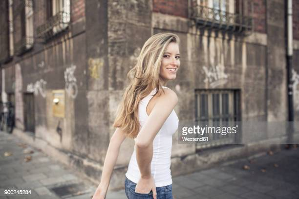 portrait of smiling young woman walking along - jeune femme blonde photos et images de collection