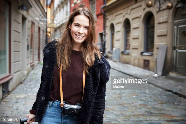 portrait of smiling young woman walking in alley amidst buildings - jak jas stockfoto's en -beelden