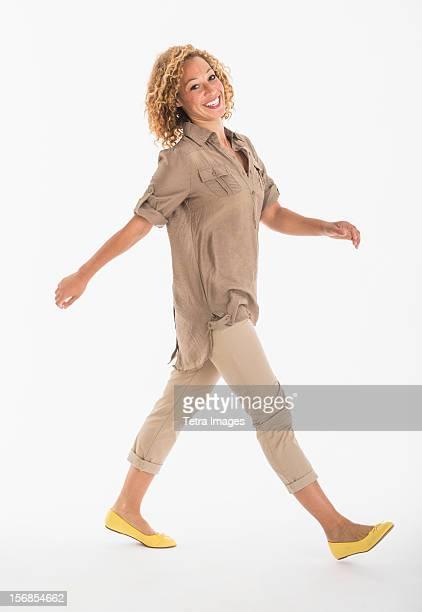 Portrait of smiling young woman walking, studio shot