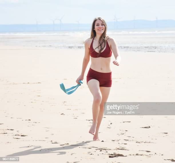 portrait of smiling young woman walking with belt running on beach - rogers arena fotografías e imágenes de stock
