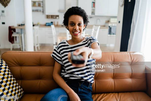 portrait of smiling young woman watching tv at home - ボーダーシャツ ストックフォトと画像