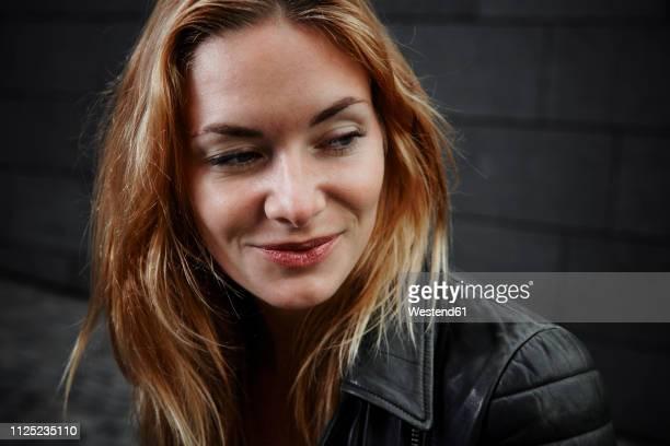 portrait of smiling young woman wearing biker jacket - seitenblick stock-fotos und bilder