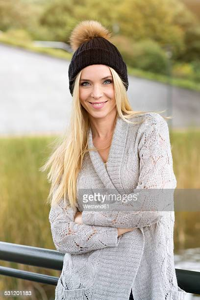 Portrait of smiling young woman wearing bobble hat and cardigan