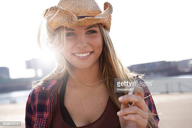 portrait of smiling young woman wearing cowboy hat - beautiful women smoking cigarettes stock photos and pictures