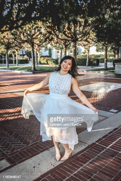 portrait of smiling young woman wearing dress while standing on footpath - ephraim lem stock pictures, royalty-free photos & images