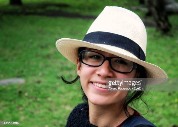 Portrait Of Smiling Young Woman Wearing Eyeglasses And Hat At Public Park