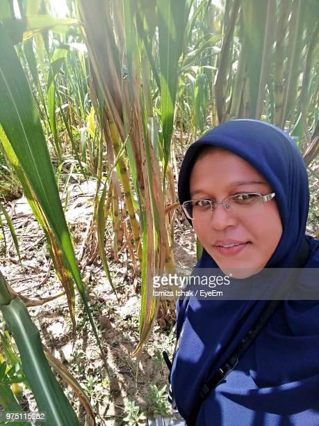 Portrait Of Smiling Young Woman Wearing Eyeglasses And Hijab On Field
