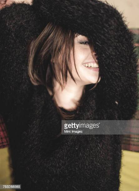 portrait of smiling young woman wearing fluffy black jumper, arms raised over head. - female hairy arms stock photos and pictures
