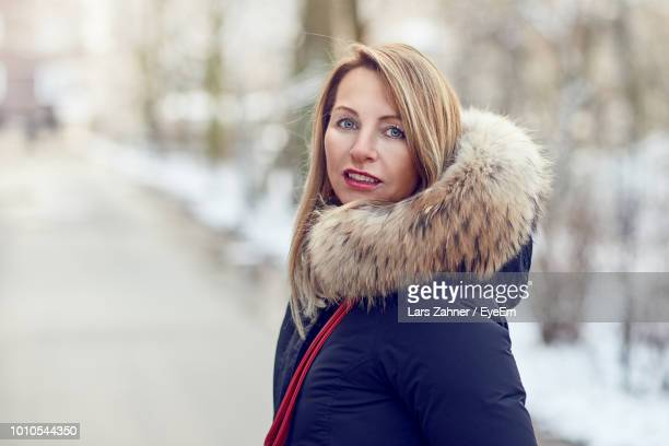 portrait of smiling young woman wearing fur coat during winter - fur jacket stock pictures, royalty-free photos & images