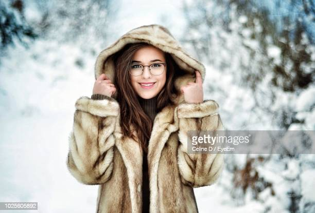 portrait of smiling young woman wearing fur coat during winter - fur coat stock pictures, royalty-free photos & images