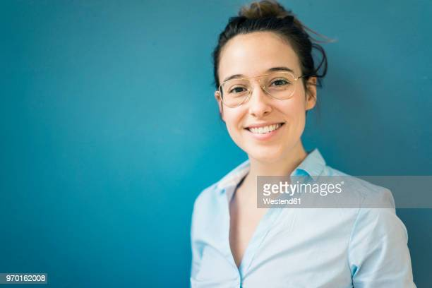 portrait of smiling young woman wearing glasses in front of blue wall - blouse ストックフォトと画像