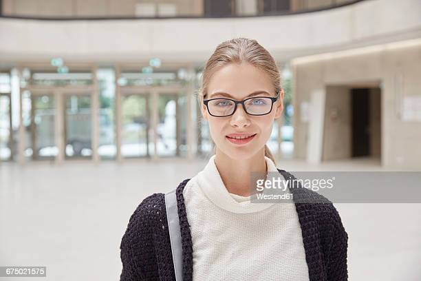 portrait of smiling young woman wearing glasses - blonde glasses stock-fotos und bilder