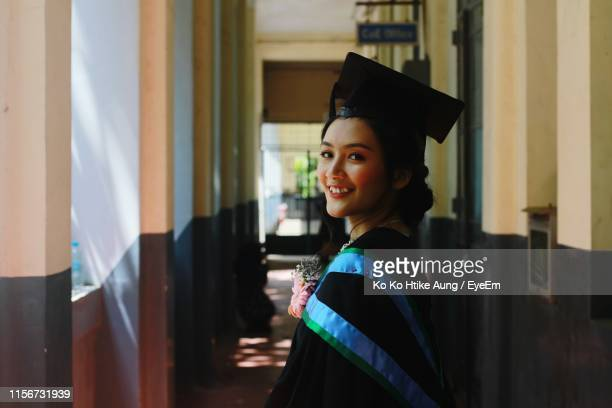 portrait of smiling young woman wearing graduation gown standing in corridor of building - ko ko htike aung stock pictures, royalty-free photos & images