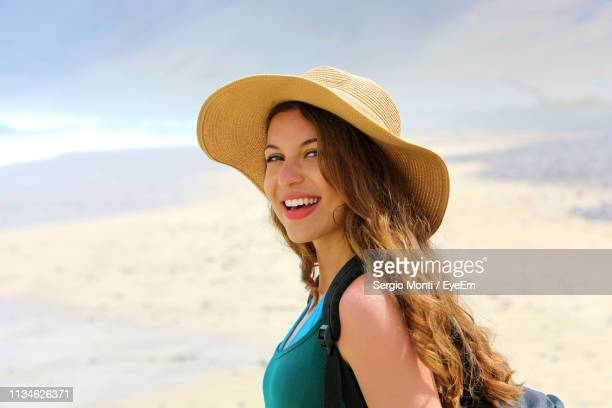 portrait of smiling young woman wearing hat at beach - one young woman only stock pictures, royalty-free photos & images