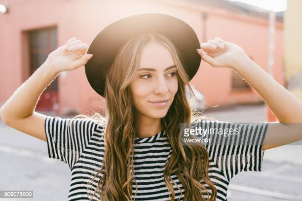 portrait of smiling young woman wearing hat - lang haar stockfoto's en -beelden