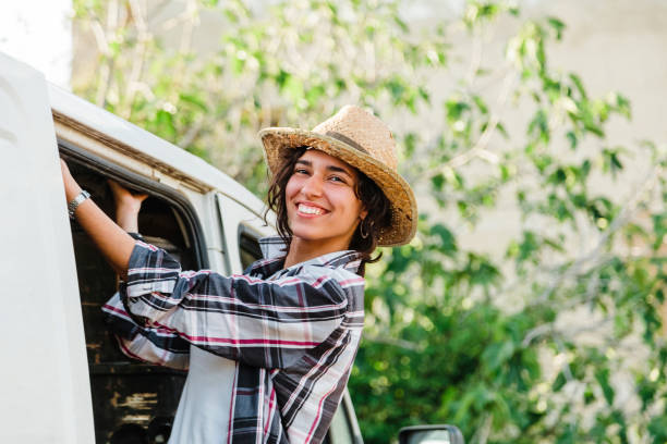 Portrait Of Smiling Young Woman Wearing Hat Standing By Car