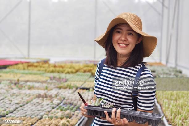 portrait of smiling young woman wearing hat standing in greenhouse - metthapaul stock photos and pictures