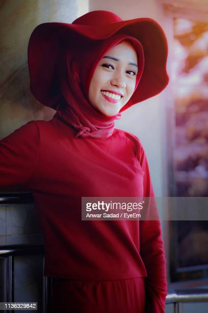 Portrait Of Smiling Young Woman Wearing Hijab And Red Hat