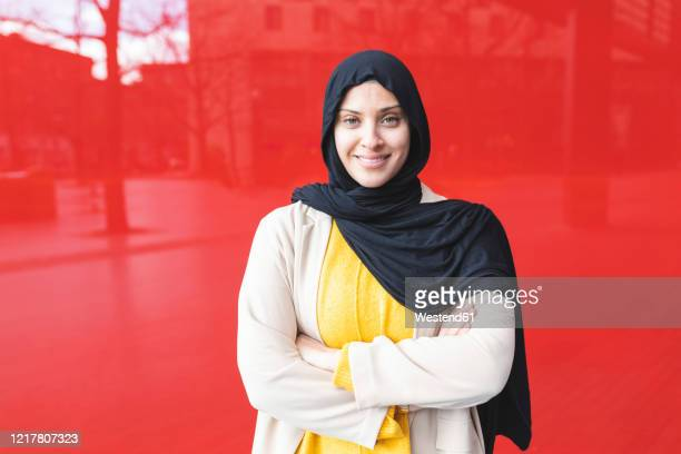 portrait of smiling young woman wearing hijab in front of red glass pane - scarf stock pictures, royalty-free photos & images