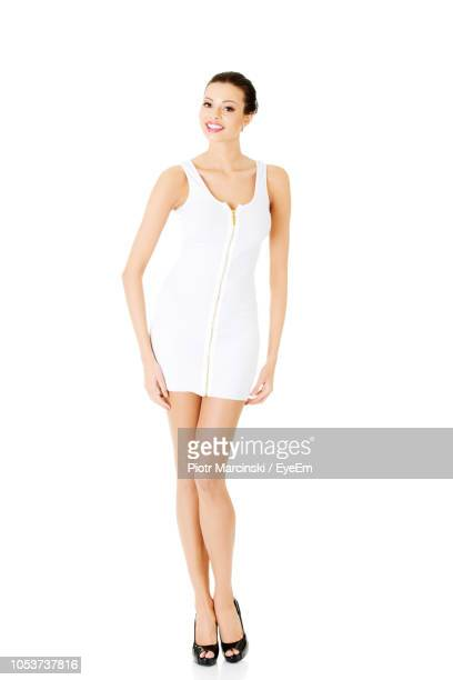 portrait of smiling young woman wearing mini dress while standing against white background - miniklänning bildbanksfoton och bilder