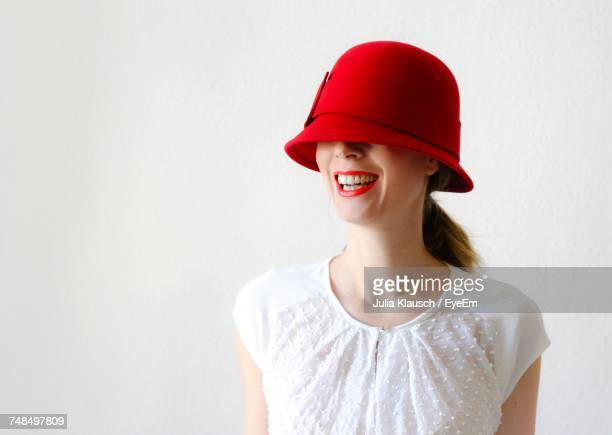 portrait of smiling young woman wearing red hat against white background - hoofddeksel stockfoto's en -beelden