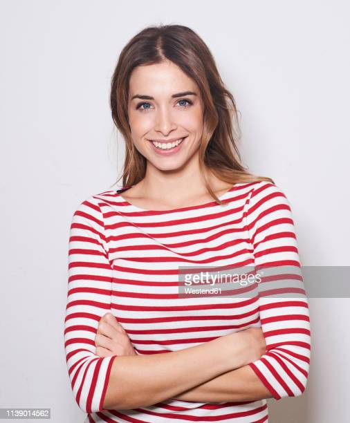 portrait of smiling young woman wearing red-white striped shirt against light background - waist up stock pictures, royalty-free photos & images