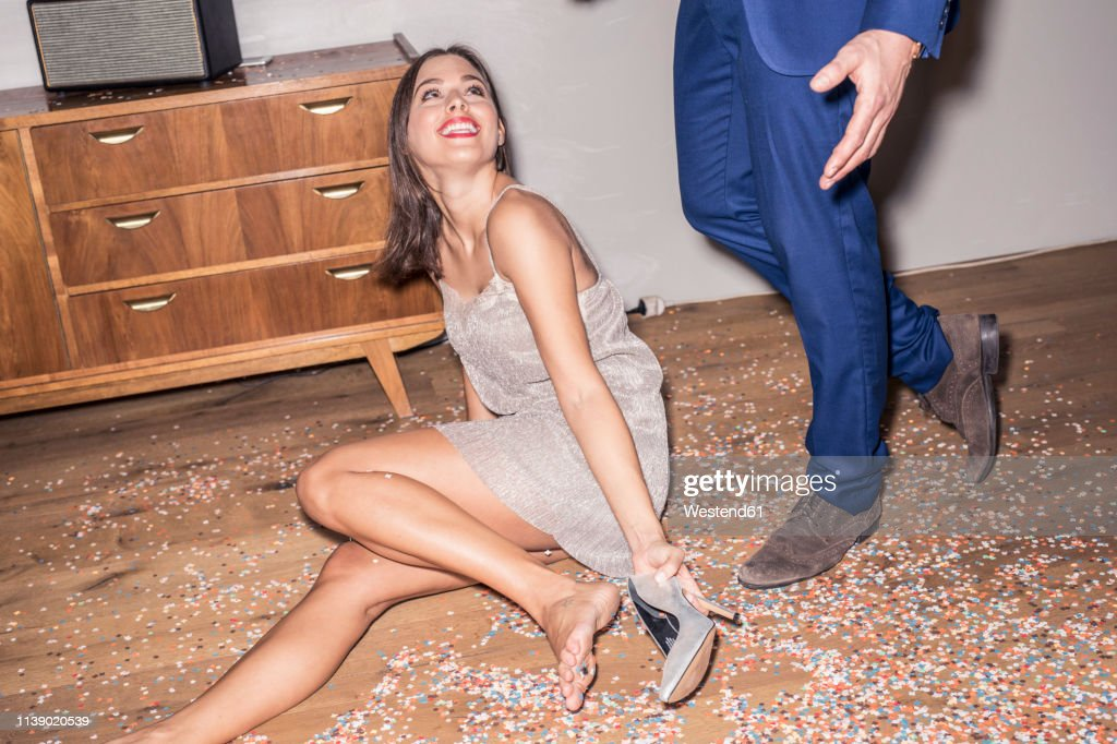 Portrait of smiling young woman wearing silver evening dress sitting on the floor in between confetti : Stock Photo