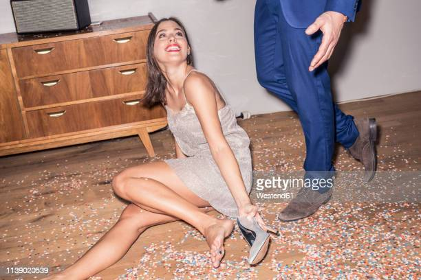 portrait of smiling young woman wearing silver evening dress sitting on the floor in between confetti - silver shoe stock photos and pictures