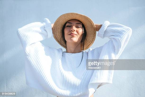 portrait of smiling young woman wearing straw hat - luz del sol fotografías e imágenes de stock