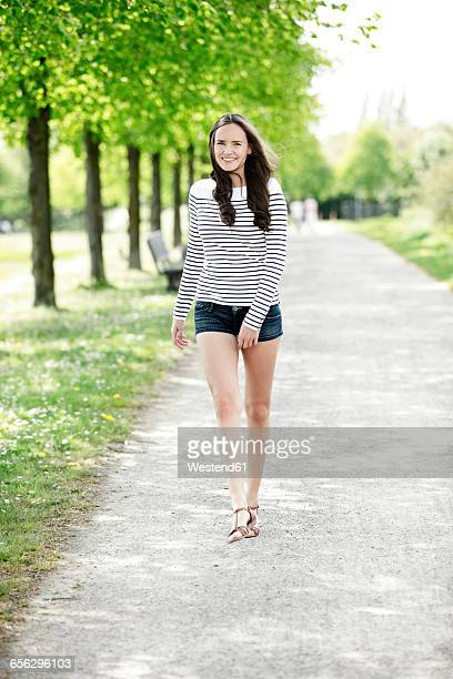 portrait of smiling young woman wearing striped sweatshirt and hot pants - hot pants stock-fotos und bilder